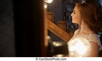 Beautiful bride stands in front of a mirror with lights in a loft interior