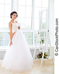 Beautiful bride-to-be trying her dress in shop - Young...