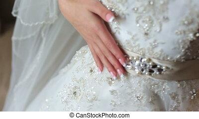 Beautiful bride touching her lace wedding dress close up