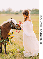 Beautiful bride walks with little poni at the sunny field