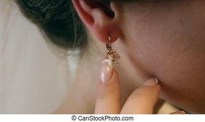 beautiful bride wears an earring in the mirror