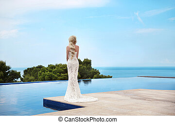 Beautiful Bride wedding portrait. Elegant blond woman with long wavy hair wearing in white fashion mermaid dress.