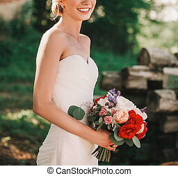 bride with a bouquet of flowers on a blurred background of the Park.