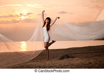 Beautiful bride with a long veil on the beach at sunset
