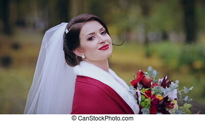 Beautiful bride with a wedding bouquet in the park