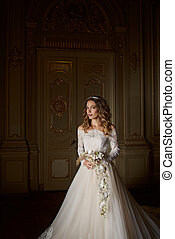 Beautiful bride with bouquet in luxury interior in the Baroque style.