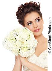 Portrait of young beautiful bride with stylish make-up and hairdo looking upwards, over white background