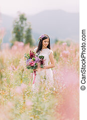 Beautiful bride with flowers on the field. Mountains background