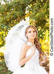 Beautiful bride with stylish make-up in white dress