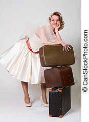 Beautiful bride with suitcases on a white background in the studio