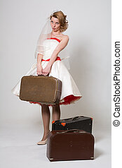 Beautiful bride with suitcases sad