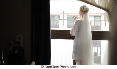 beautiful bride with veil on the terrace in the rain