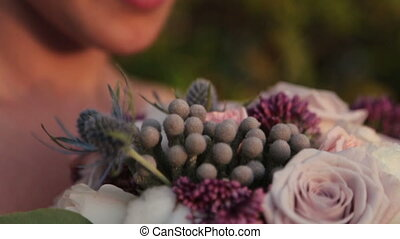 Beautiful bride with wedding bouquet in hands close up