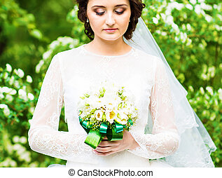 Beautiful bride with wedding bouquet of flowers outdoors in spring park.