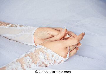 Beautiful bride's hands with manicure in white gloves