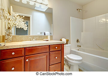 Beautiful  bright bathroom with cherry wood cabinets