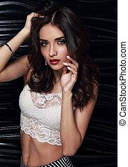 Beautiful bright evening makeup female model posing in white fashion white top on dark black background