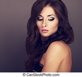 Beautiful bright makeup woman with curly long hair style and pink lipstick looking down