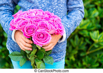 Beautiful bright pink roses in child's hands