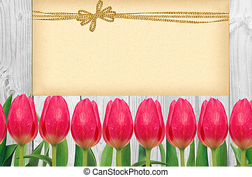 Beautiful bright tulips and card with golden bow on wooden background
