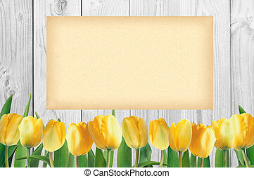 Beautiful bright yellow tulips on wooden background and empty paper card
