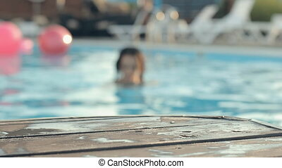 Beautiful brown-eyed girl with long hair wearing a bikini swimming in a pool and leaning her elbows on a wooden pier