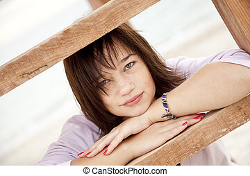 Beautiful brunet girl near wood stairs at outdoor.