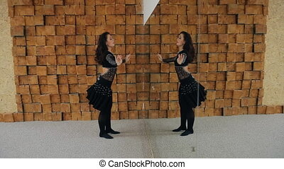 Beautiful brunette acts oriental dance in front of mirror.