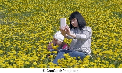Beautiful brunette and girl are resting in a city park. Mother makes selfie with her little daughter. Slow motion