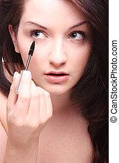 Beautiful brunette applying mascara/makeup