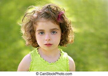Beautiful brunette blue eyes little girl portrait on grass