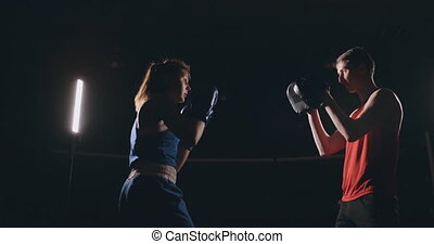 Beautiful brunette boxer working out blows to the paws with...