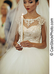 Beautiful brunette bride holding a candle in church during wedding ceremony