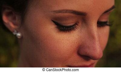 Beautiful brunette bride looks into the camera close up.