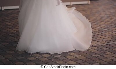 Beautiful brunette bride turning around in white dress. Happy woman in wedding day posing, enjoying the celebration.