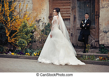 Beautiful brunette bride walking down old street, while the groom is leaning against the wall