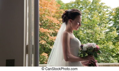 Beautiful brunette bride with wedding bouquet standing near the window