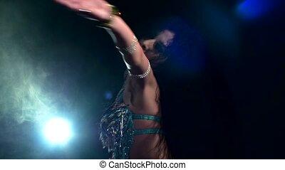 Beautiful brunette dancing belly dance, on black, back light