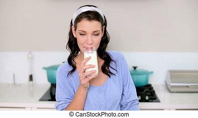 Beautiful brunette drinking a glass of milk