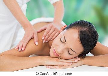 Beautiful brunette enjoying a back massage at a luxury spa