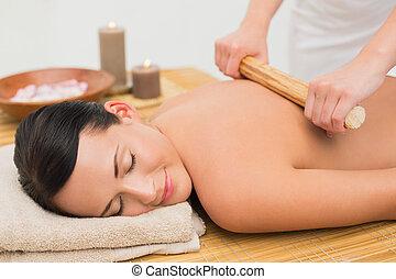 Beautiful brunette enjoying a bamboo roller massage in the...