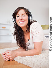 Beautiful brunette female using headphones while lying on a carpet in the living room