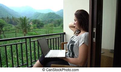 beautiful brunette freelancer woman sitting on balcony in...