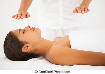 Beautiful brunette getting reiki therapy at the health spa