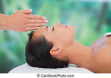 Beautiful brunette getting reiki therapy at a luxury spa