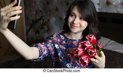Beautiful brunette girl doing selfie with red flowers tulips on black smatfon.