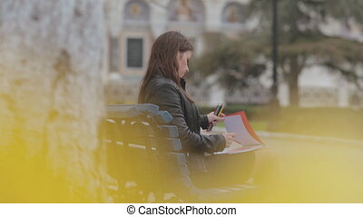 Beautiful brunette girl drawing in the album with bright pencils sitting on bench in park near the church