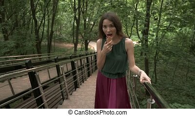 Beautiful brunette girl eating ice cream cone in the park. Slow motion shot