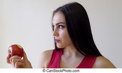 beautiful brunette girl eats Red Apple on a white