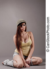 Beautiful brunette girl folding her legs on the floor